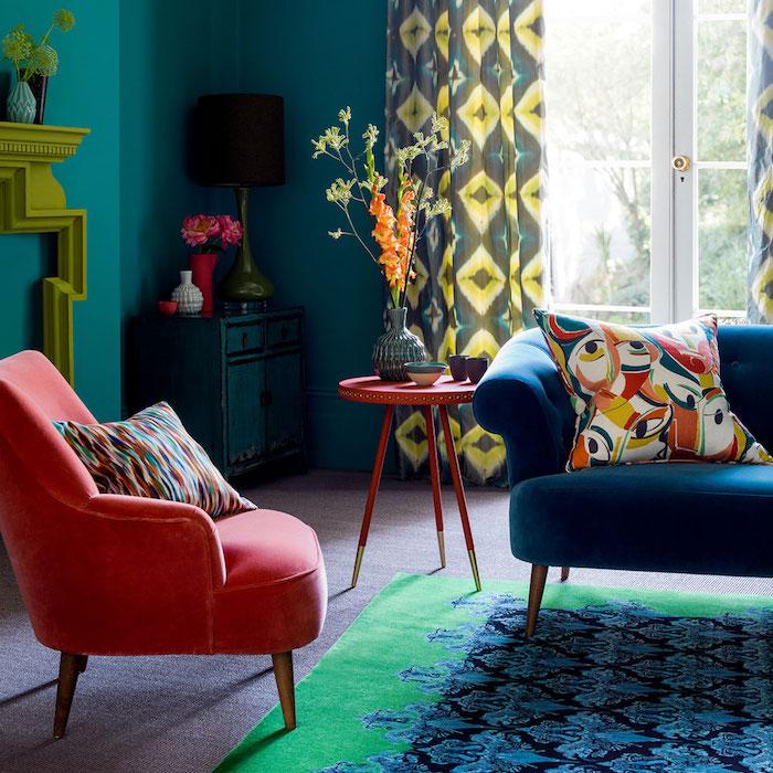 bleue t rouge déco salon avec peinture bleu canard, canapé bleu et tapis bleu et vert, fauteuil rouge, cheminée design, rideaux et coussins décoratifs colorés
