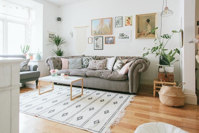salon cocooning, canapé gris, parquet bois clair, tapis blanc à motifs géométriques gris, coussins decoratifs gris, rose, marron, vert, blanc, deco murale cadres artistiques