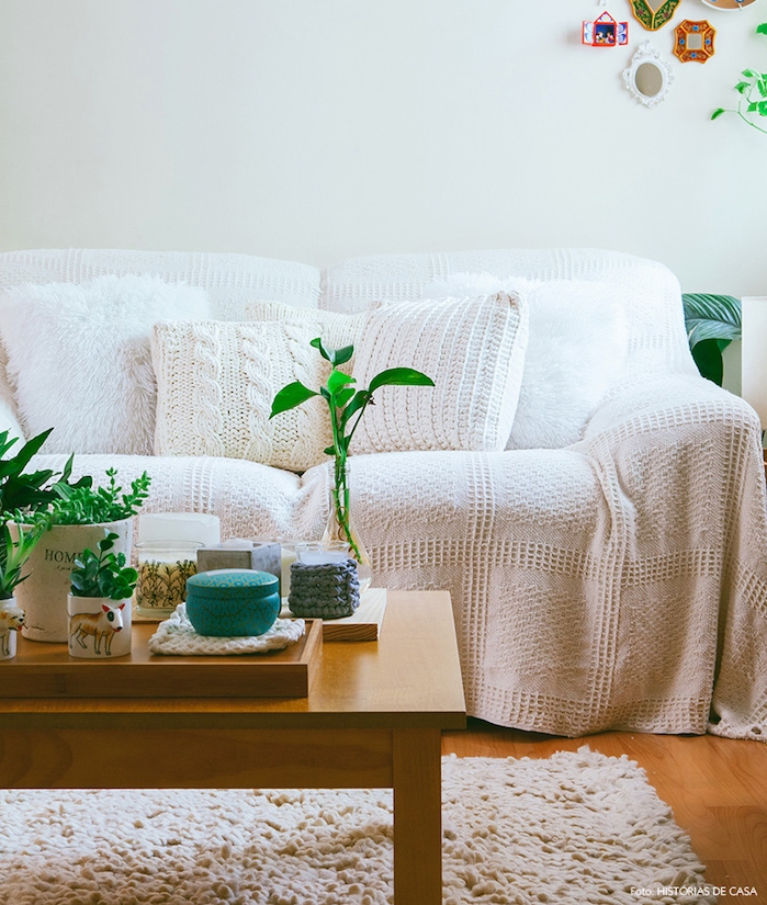 salon cocooning, tapis fourrure blanc, table basse en bois, canapé avec couverture tricotée blanche, taie d oreiller tricotés, plantes vertes