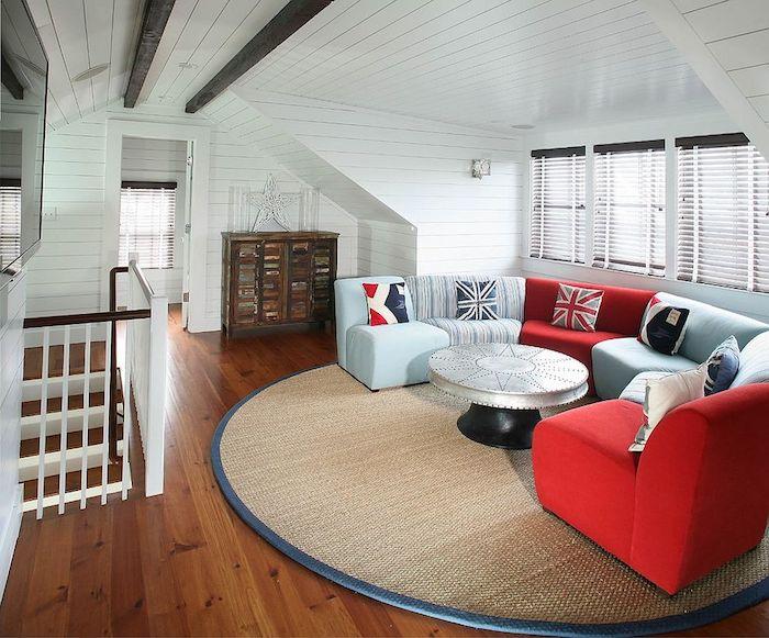 idée deco bleue et rouge, canapé bleu, rouge, table basse design, tapis rond beige, parquet en bois clair, mur et plafond en lambris blanc