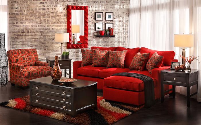 canapé d angle rouge, fauteuil et coussins décoratifs en rouge et marron, tapis coloré, table et parquet marron foncé, mur d accent en briques
