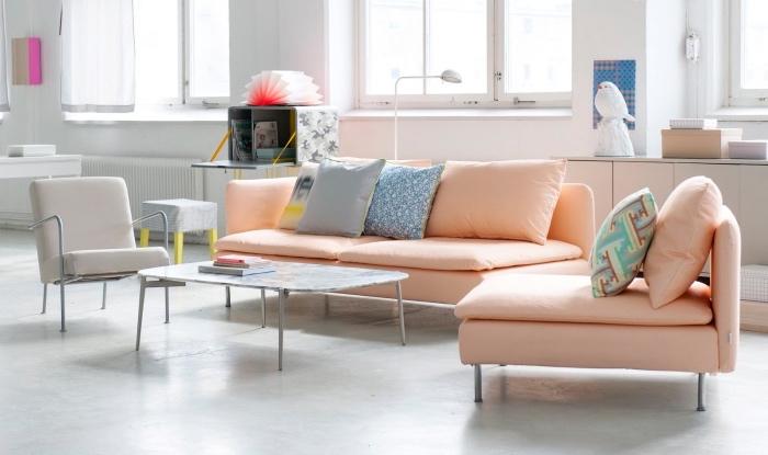 mobilier scandinave pastel, canapé saumon, fauteuil gris, sol blanc et murs blancs, table basse, salon spacieux