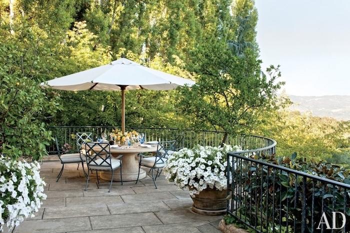 aménager sa terrasse zen en dalles de béton, végétation florissante, plantes vertes, pétunias blanches, table en pierre, chaises metalliques noires, parasol blanc