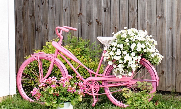 idee creation deco simple, un vélo repeint en rose recyclé, décoration de fleurs dans le jardin, cour arrière