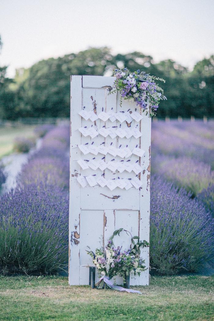 une porte vintage en bois usé avec des étiquettes blanches invités et bouquets de fleurs, champ de lavande, plan de table original