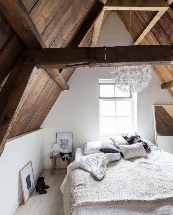 deco esprit scandinave, idée déco chambre sous combles, ossature, poutres apparentes, linge de lit blanc, coussins blanc et blei, suspension originale, parquet clair