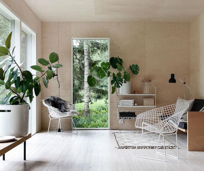 salon cocooning, parquet clair, chaises metalliques blanches, banc en bois, coussins gris, plantes vertes, revêtement mural en bois