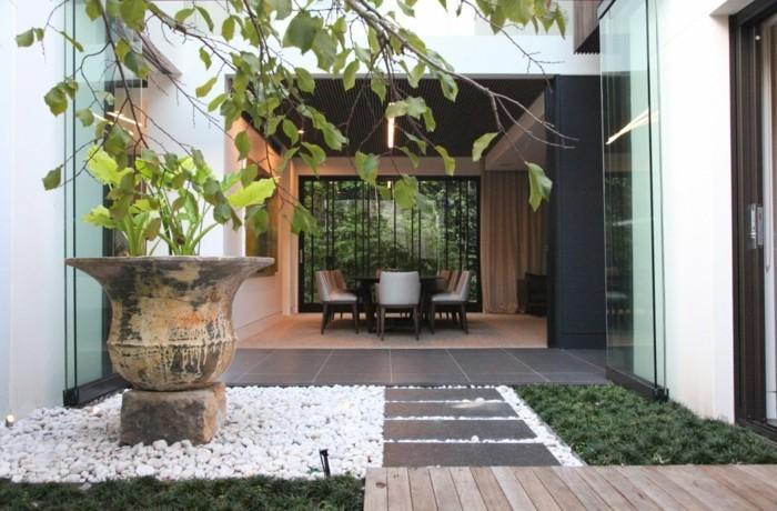 idee terrasse amenagement, chemin de carrelage, bois et zone avec galets blancs, plante couvre sol vert