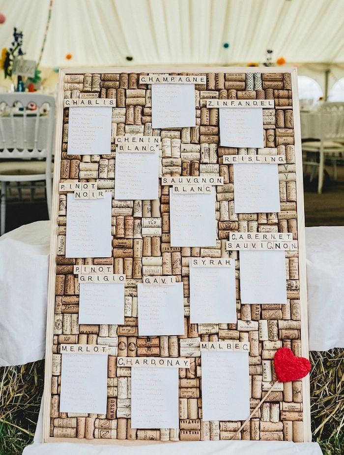 plan de table pour mariage tableau avec fond de bouchons de liège, petites listes blanches invités, coeur rouge