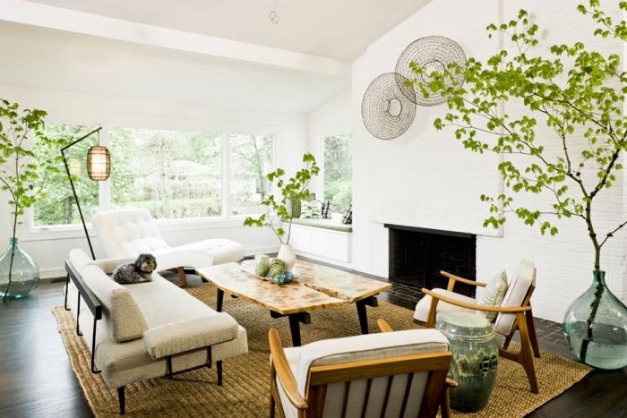 idée décor blanc dans un salon scandinave, tapis beige, canapé en metal, coussin d assise blanc, table design, fauteuils chaise-longue blanc, cheminée, deco de plantes