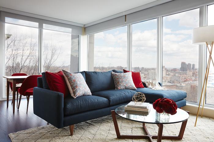 idée comment décorer un salon bleu et rouge, canapé bleu marine, coussins rouges et à motifs floraux, tapis blanc cassé, table basse en bois et verre, coin repas avec table bois et chaises couleur bordeau