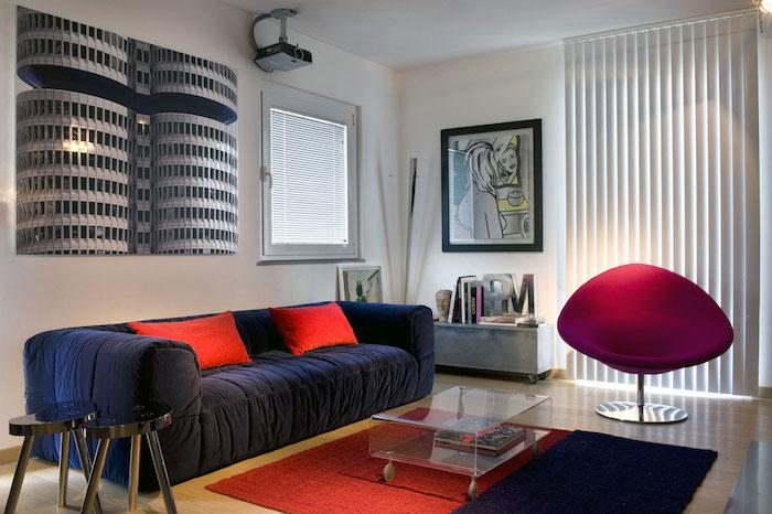 idée de mur couleur blanche, canapé bleu marine, paré de coussins rouges, fauteuil couleur framboise, table en plastique, tapis bleu et rouge, deco murale originale