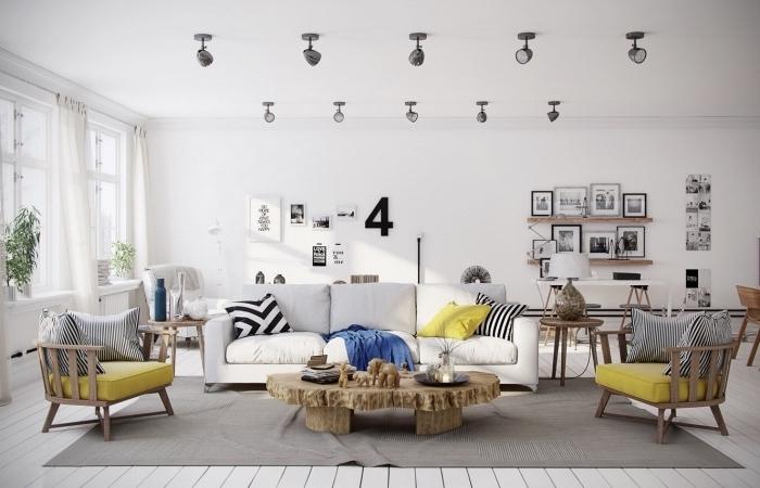 deco salon scandinave, tapis gris, canapé blanc cassé, chaises en bois avec coussins d assise jaune, table bois rustique, deco murale de dessins et photographies en noir et blanc