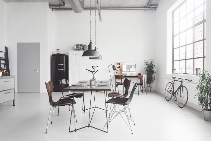 meubles scandinaves dans une salle à manger scandinave, industrielle,, table et chaise en ois et metal marron, suspensions industrielles, buffet scandinave blanc, frigo noir, vélo, coin travail, bureau