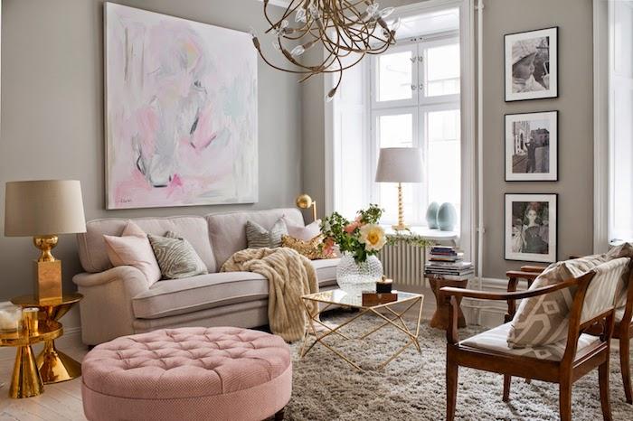 salon aux murs taupe, table ronde à design doré, bouquet de fleurs fraîche dans une vase ronde en verre