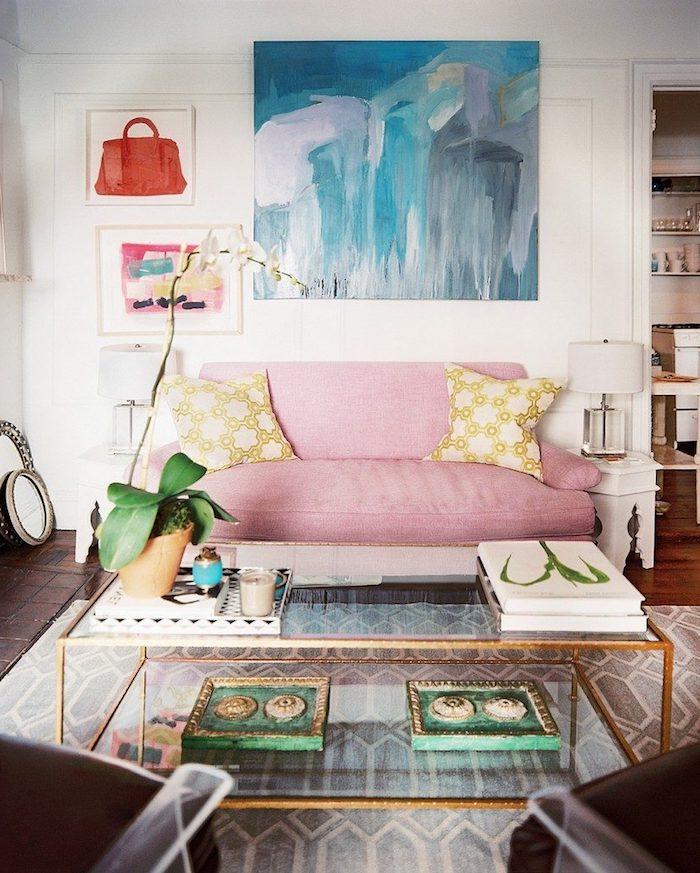 salon aux murs blancs avec peintures acryliques, fauteuils en cuir noir, lampe de chevet en blanc