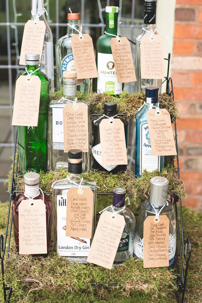 plan de tale mariage en bouteilles d alcool avec des étiquettes en papier kraft avec les noms des invités sur une étagère noire