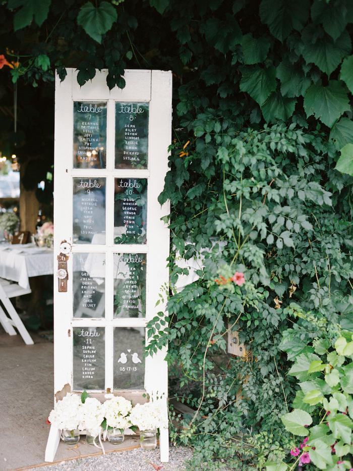 idée de plan de table mariage original, une porte vintage avec les noms des invités écrits sur les carreaux de verre, liste écrite en feutre blanc verre, cadre naturel