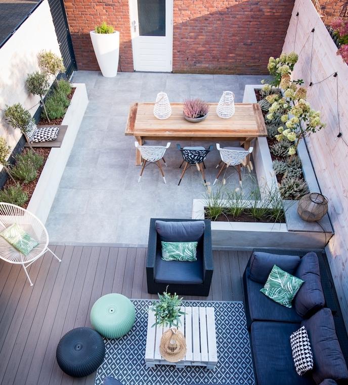 deco terrasse zen avec coin détente, table basse en palette blanche, canapé et fauteuil gris anthracite, tapis noir et blanc, revêtement bois et dalles de béton, coin salle à manger bois, arbres etarbustes