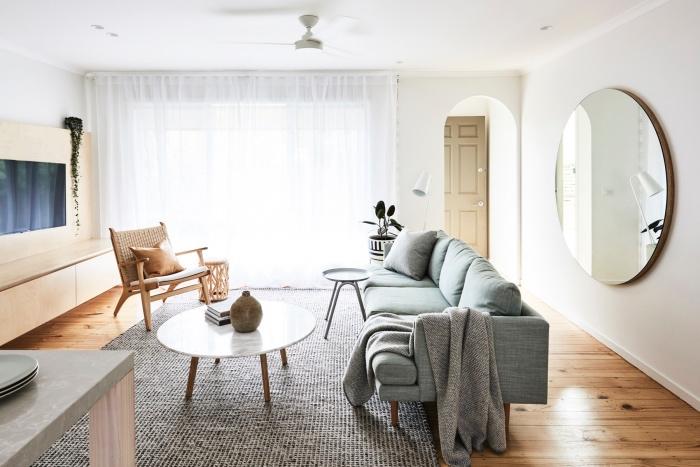 deco salon moderne, porte et chaise beige, canapé bleu-gris sur un fons blanc, miroir rond, tapis gris, parquet clair, meuble tv en bois