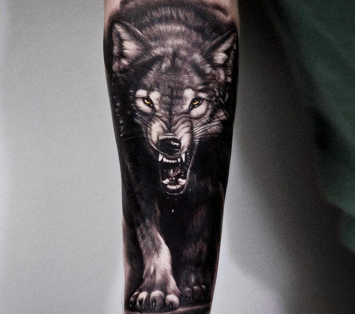 symbole tatouage, dessin sur la peau pour homme, image de loup aux yeux jaunes et visage féroce sur le bras