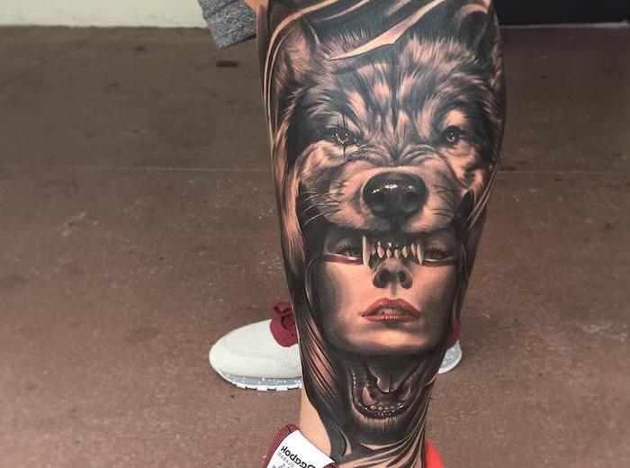 homme tatoué, baskets en blanc et rouge modèle homme, tatouage sur jambe avec tête femme loup