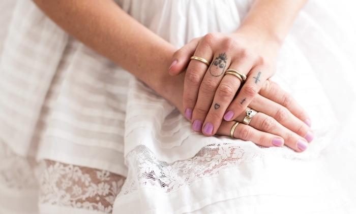 manucure rose ongles courts, petits tatouages sur les doigts féminins, bagues en or pour femme, robe blanche rayée