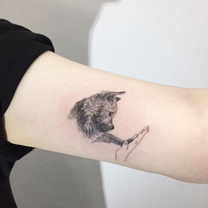 amitié entre homme et animaux, petit tatouage à design mignon sur le bras, idée dessin en encre