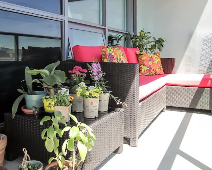idee terrasse blanche avec canapé et table de service en rotin, salon tressé, coussins d assise dossier rose et coussins décoratifs colorés, plantes vertes