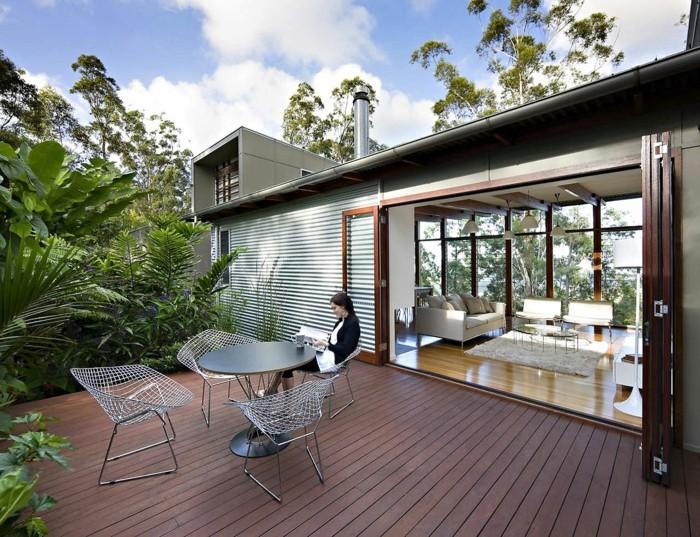 salon moderne qui s ouvre sur une terrasse zen en bois composite marron, table et chaises design, bordure de plantes vertes