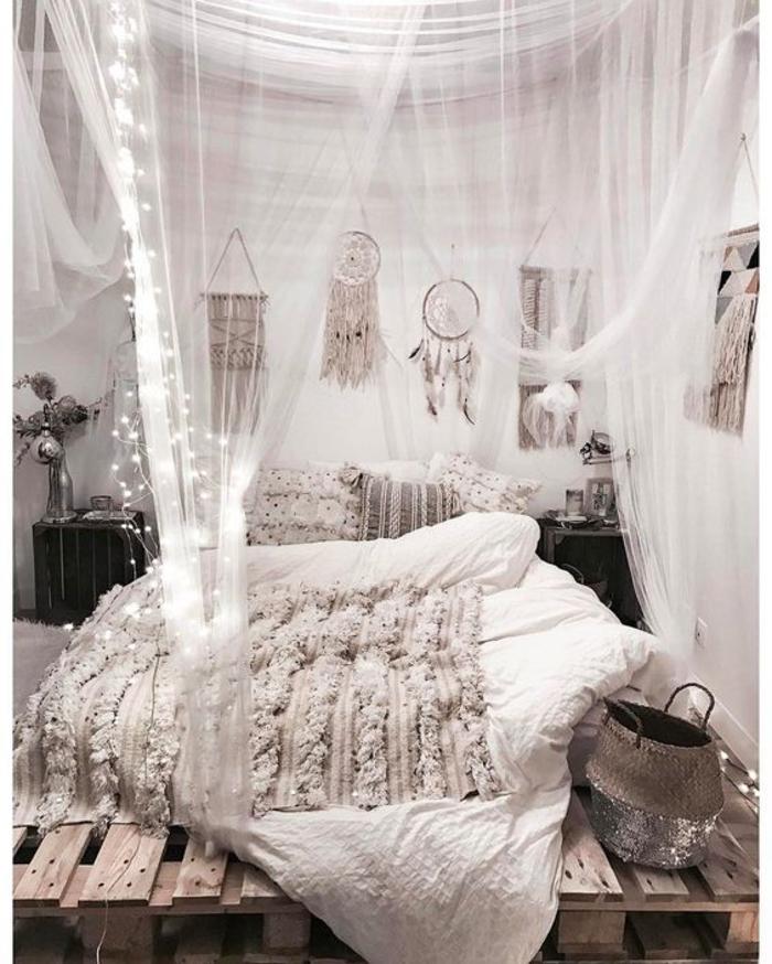 une chambre à coucher bohème chic avec un lit palette à baldaquin et à lumières led