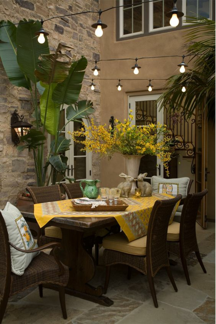 aménager un petit jardin avec des meubles en rotin et des guirlandes avec ampoules lumineuses