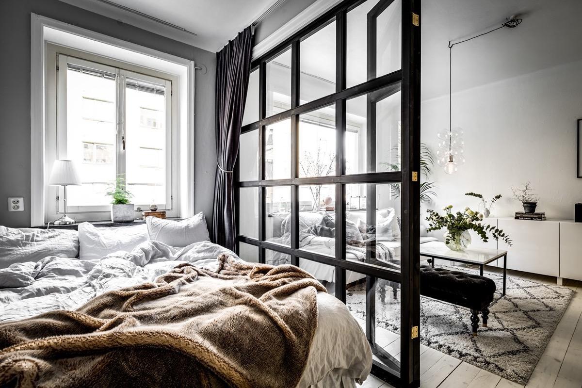 idee deco cocooning, linge de lit blanc, couverture en fausse fourrure marron, verrière pour séparation, ouverture sur un salon gris et blanc