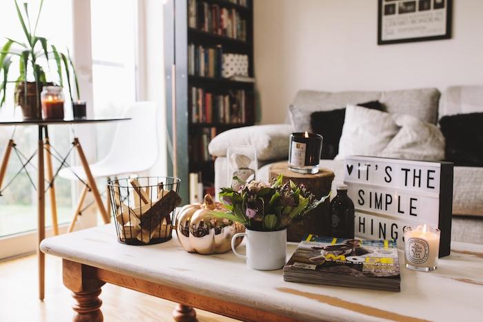 salon cocooning, canapé gris, coussins gris et noir, table basse en bois, parquet clair, decoration de magazines, citrouille dorée, bougies, bûche de bois, bouquet de fleurs