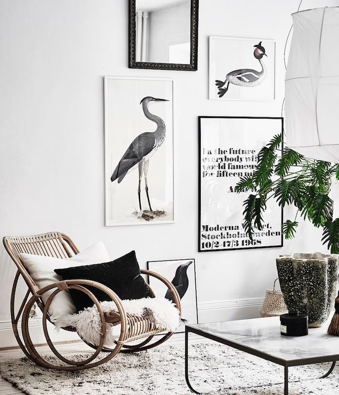 modele de tapis cocooning noir et blanc, chaise à bascule en bois, jeté de fourrure, coussin decoratif noir et blanc, tableaux décoratifs, plante verte