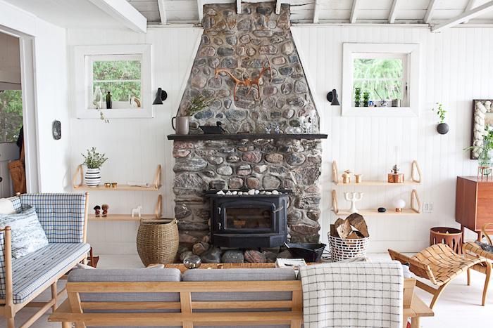 salon cocooning rustique avec cheminée en pierre, bancs en bois avec coussins d assise grises, panier en rotin, lambris blanc