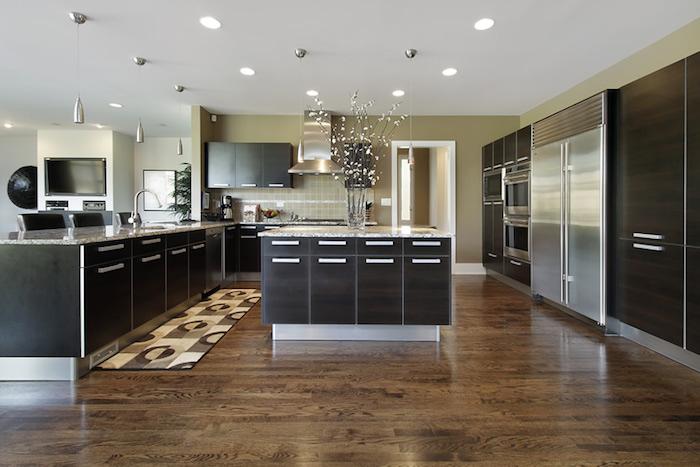 cuisine semi ouverte, lampes suspendues en métal, tapis rectangulaire à motifs géométrique jaune beige et marron