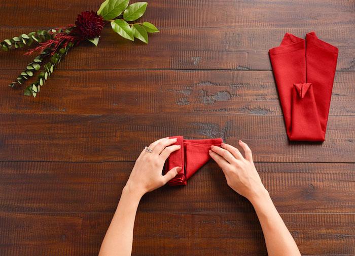 pliage serviette, comment plier une nappe de table rouge en forme animal, table en bois marron foncé