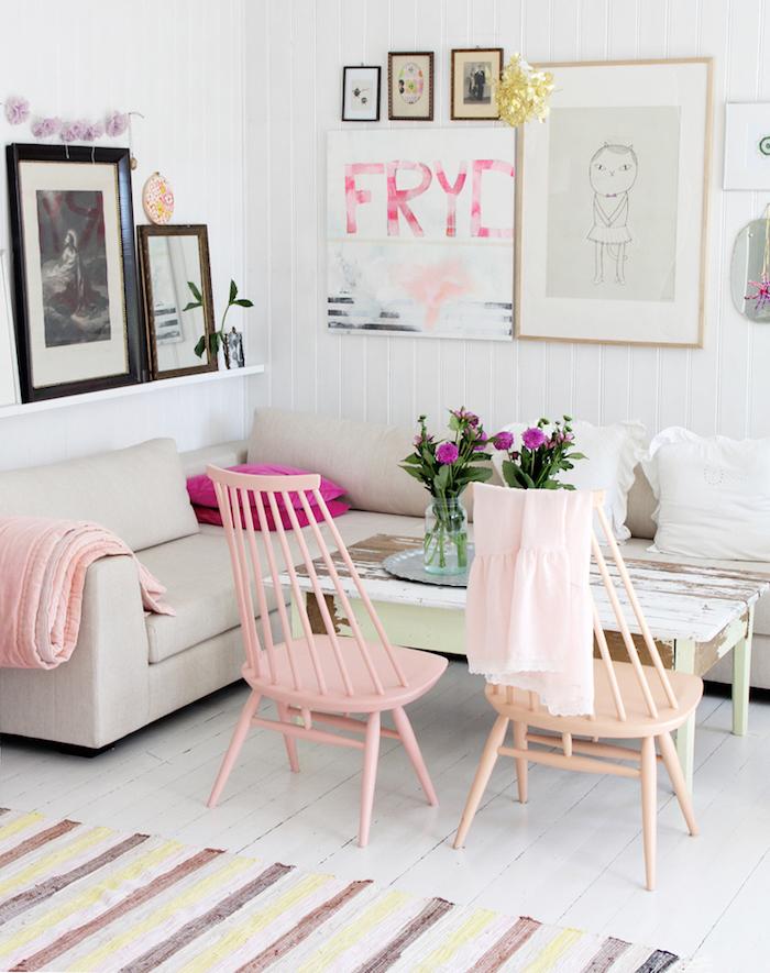 salon aux murs blancs avec cadres photos, canapé d'angle avec coussins décoratifs, table shabby chic en bois peint vert