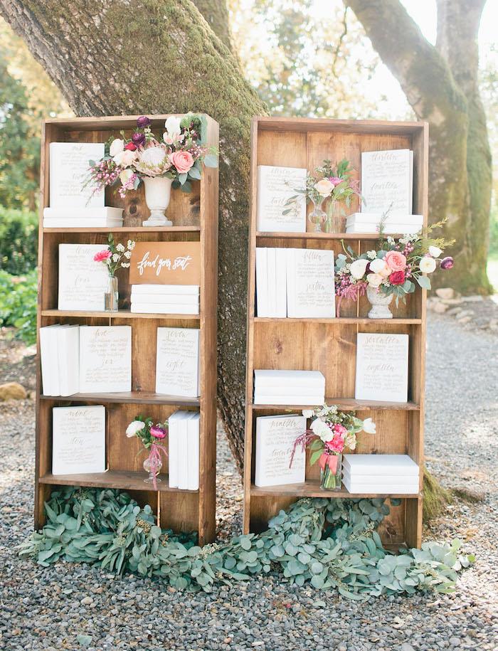 plan de table mariage en vieilles bibliothèques bois avec des livres blancs avec noms invités écrits sur la couverture, bouquets de fleurs dans des vases blancs
