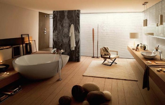 idee deco salle de bain, sol en planches, plusieurs coussins galets, baignoire à poser, long comptoir en bois