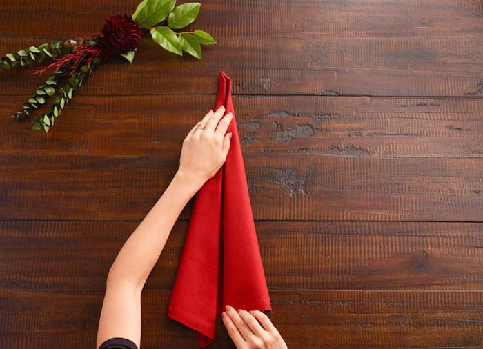 pliage serviette, bouquet décoratif de feuilles vertes, étape de pliage origami avec serviette
