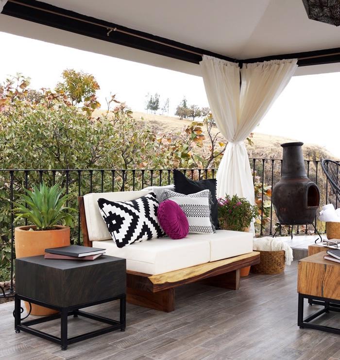 amenagement terrasse orientale, revêtement en bois marron, canapé bois et table en bois et métal, cheminée design, coussins bohème