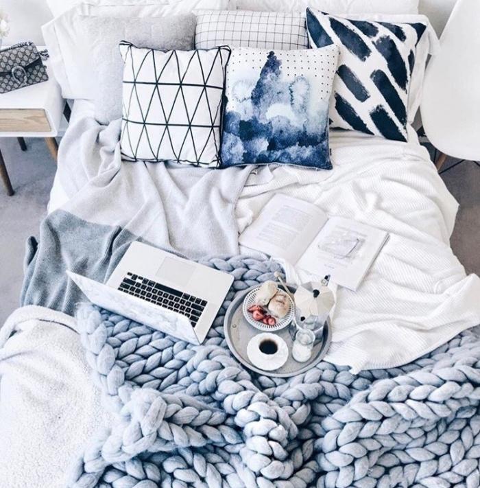 chambre cocooning avec linge de lit gris, bleu, blanc, coussins décoratifs, plaid tricoté à grosses mailles, petit déjeuner servi sur un plateau