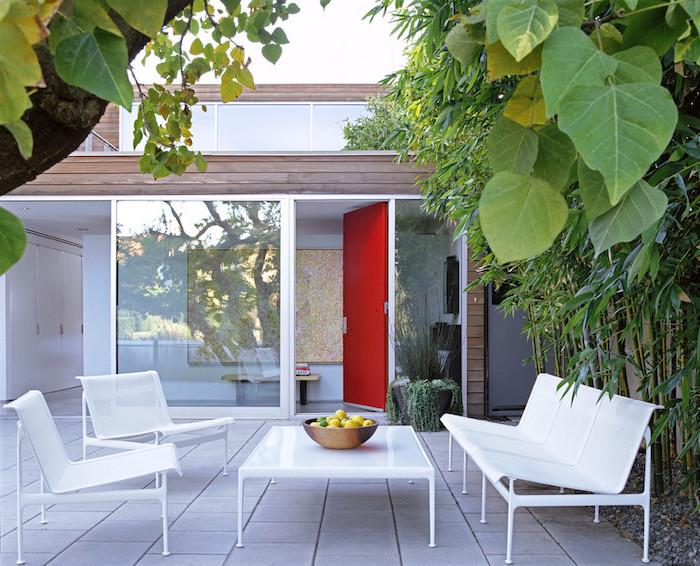 idee salon de jardin sur une terrasse accueillante, revêtement dalles de béton, table basse, canapé et chaises blancs, bambou et autres plantes