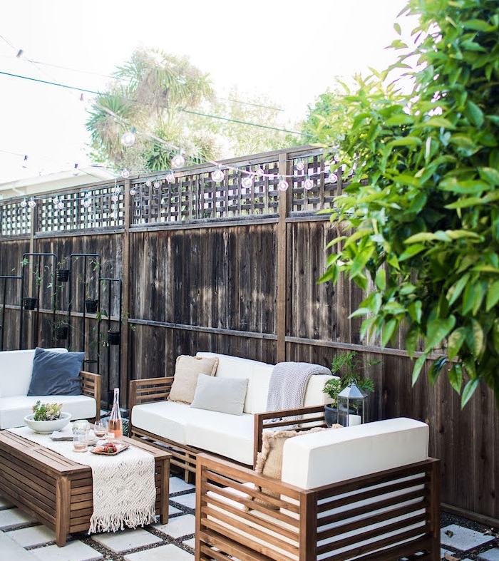 exemple idee salon de jardin, table, canapé et fauteuil en bois, coussins d assise blancs, dalles de béton sur du gravier, clôture en bois