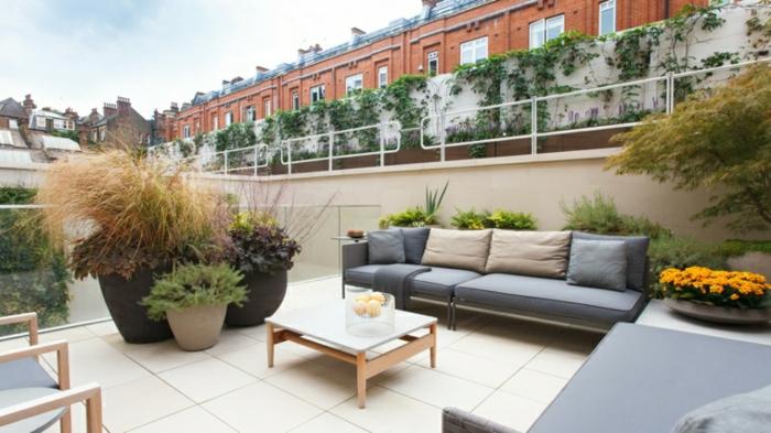 amenagement terrasse exterieure, carrelage beige, canapé gris, bacs à fleurs avec des plantes, table basse blanche
