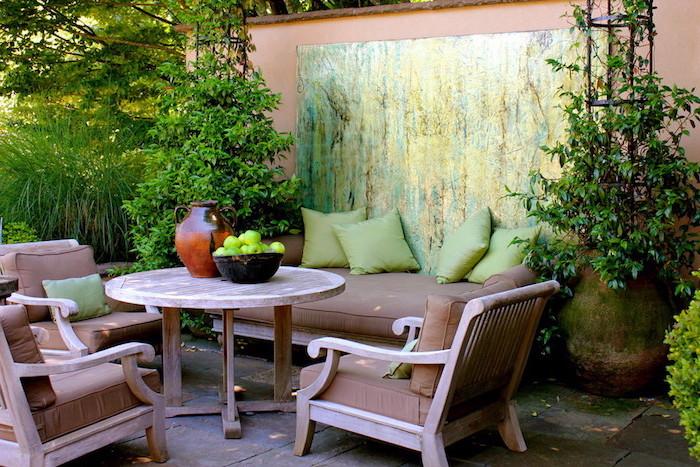 idee salon de jardin, table, fauteuils et canapé en bois avec des coussins d assise marron, coussins décoratifs verts, paysage de plusieurs plantes vertes