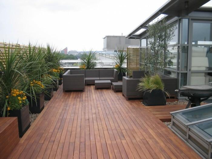 exemple idee salon de jardin, revêtement bois composite marron, canapé et tables gris anthracite, bac a fleurs, palmiers