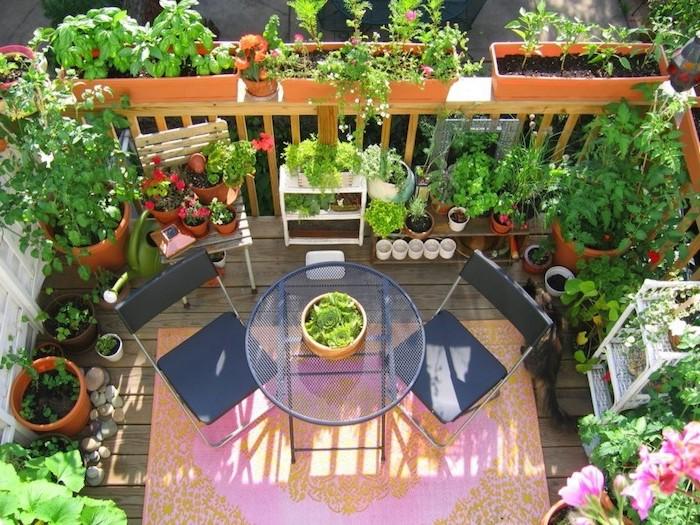 deco terrasse, balcon, tapis orange et rose, table et chaises noires, sol en bois, galets, plusieurs pots de fleurs
